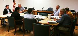 A group of people sit around a meeting table